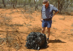 Australian farmer Stirton stands next to a ball of twisted metal, purported to be fallen space junk, on his farm in southwestern Queensland